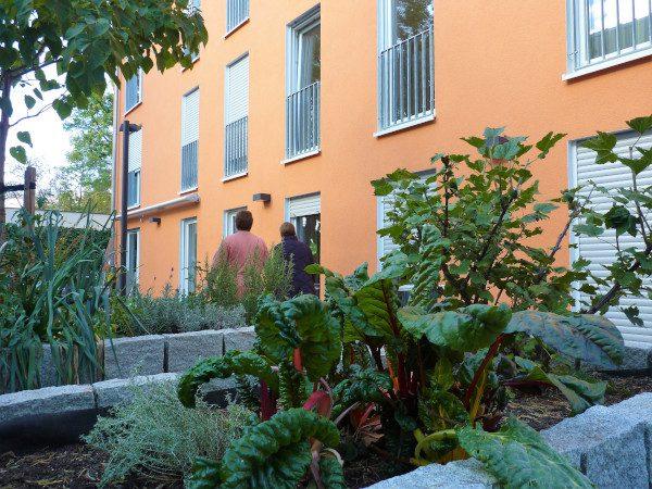 Südseite mit kleinem Garten für die Bewohner u.a. mit Hochbeet und Sitzbereich.